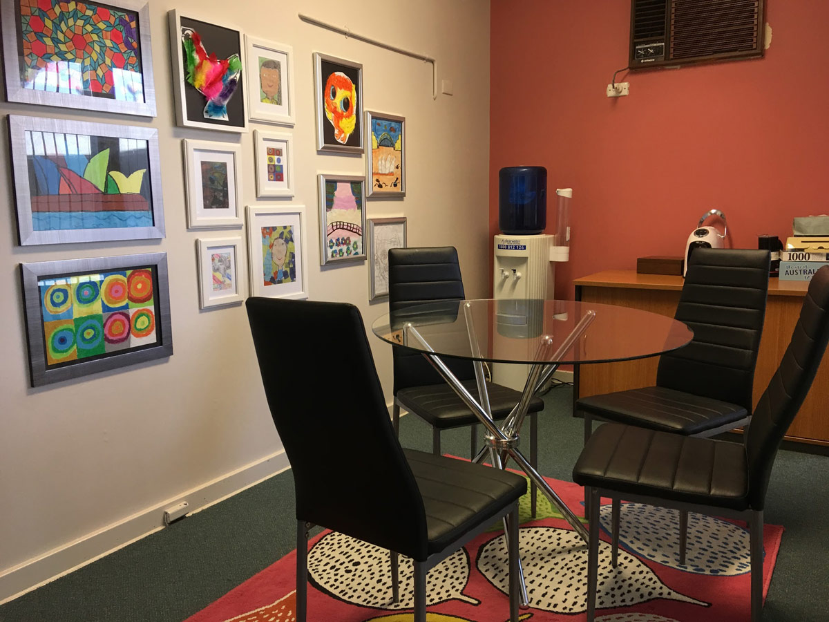 Glass table and dining style chairs with colourful rug and student artwork gallery wall