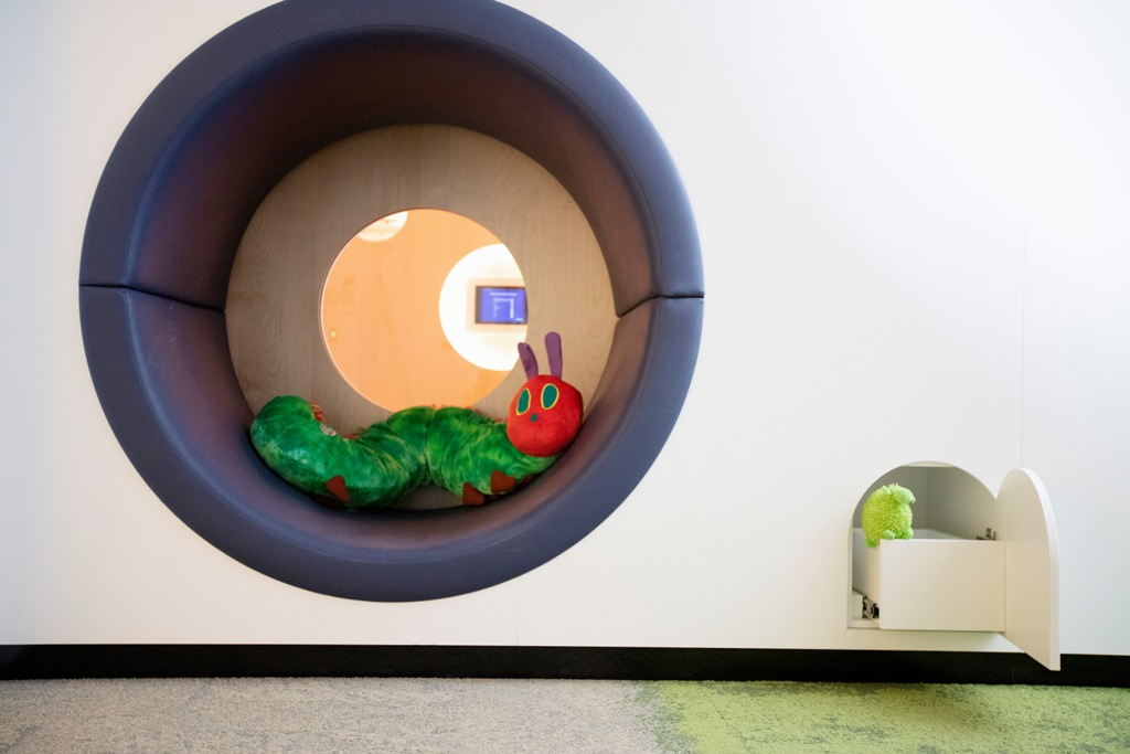 Circular wall seat with internal window and large plush caterpillar toy