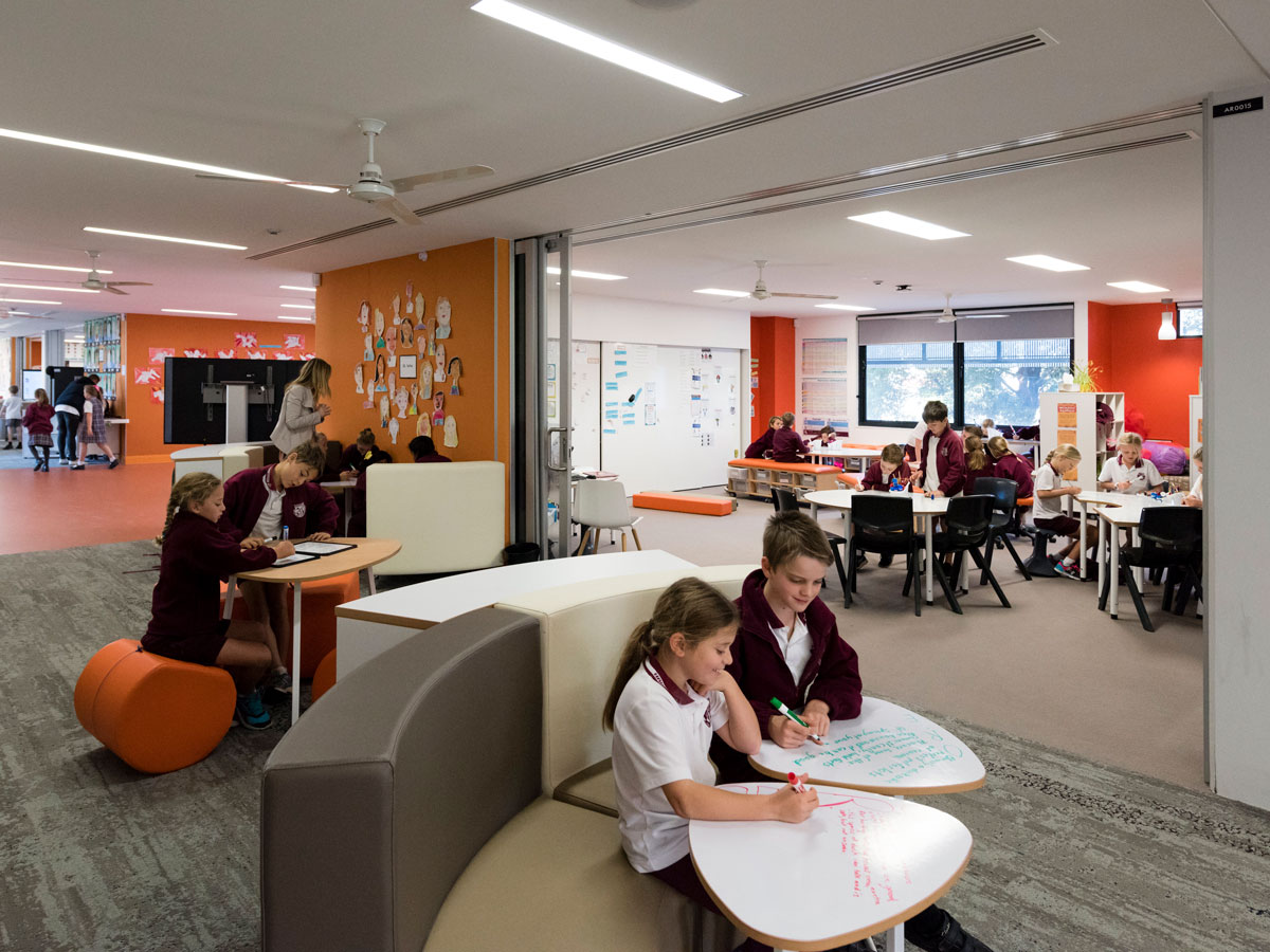 A large space that classrooms can open into with sliding doors. Assorted furniture such as ottomans, booth and individual tables with writable surfaces available for students.