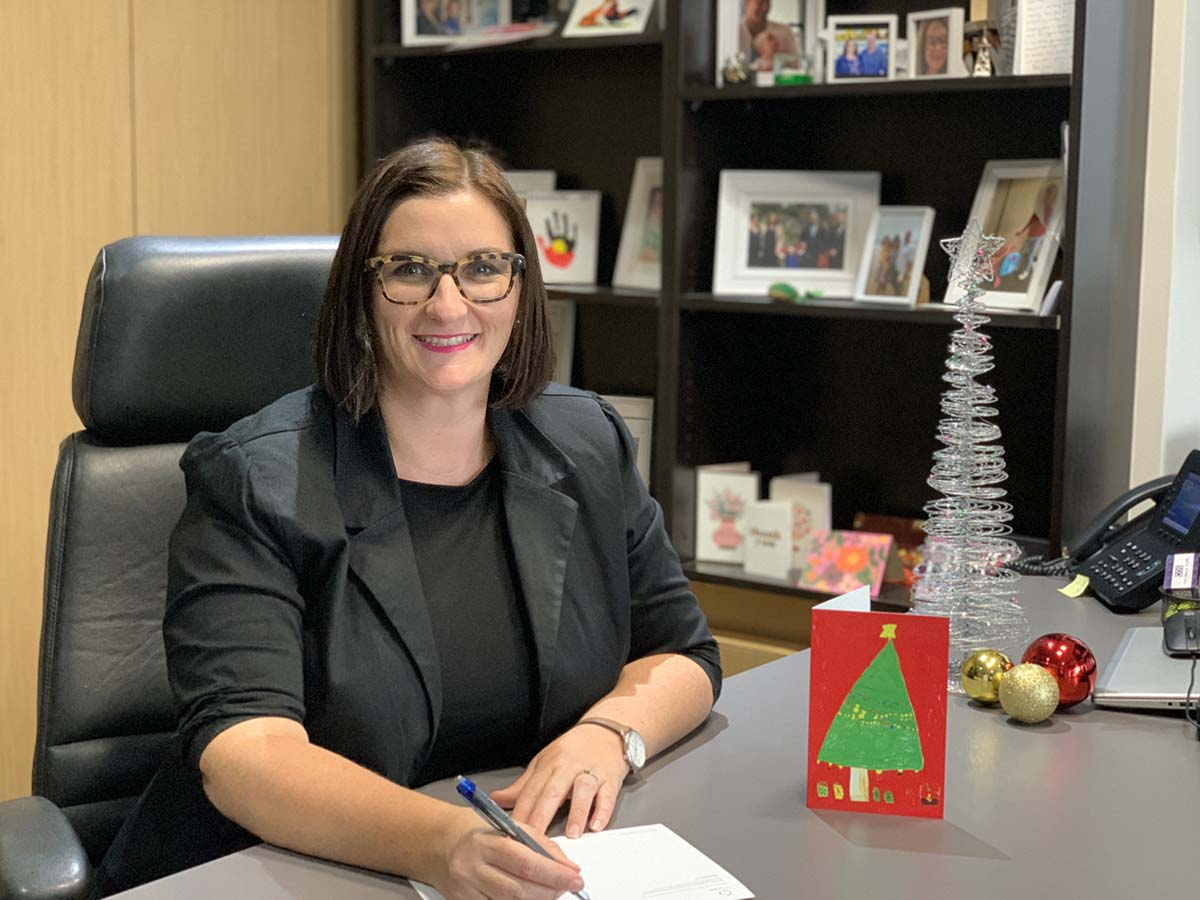 Minister Mitchell signing the Christmas card