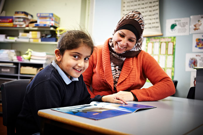 Teacher sitting next to student smiling while student looks up from reading book at desk