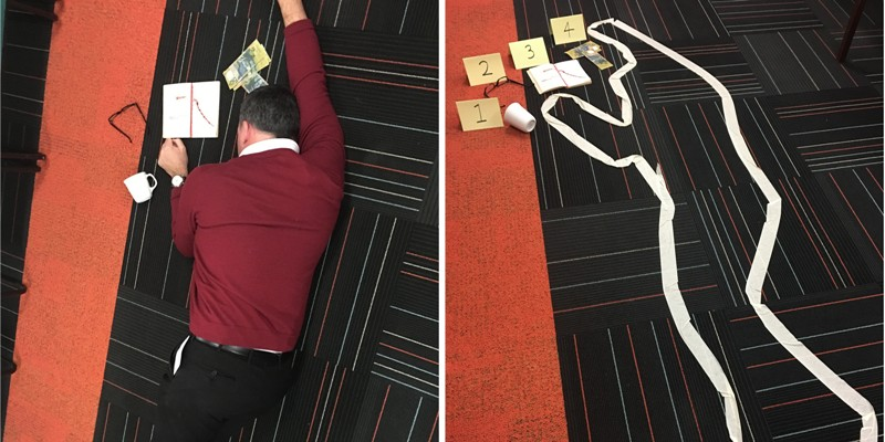A crime scene in the library, showing a male teacher lying motionless on the floor, with clues