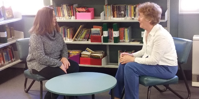 Jan speaks with a colleauge in the library