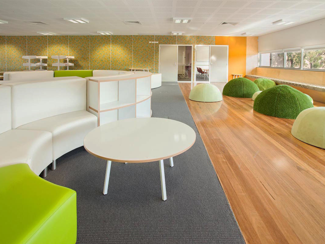 Curved light coloured bench seating with wraparound bookshelves. Padded seating along the length of the window. Large grassy domes for additional seating. Breakout rooms with glass panels for visibility