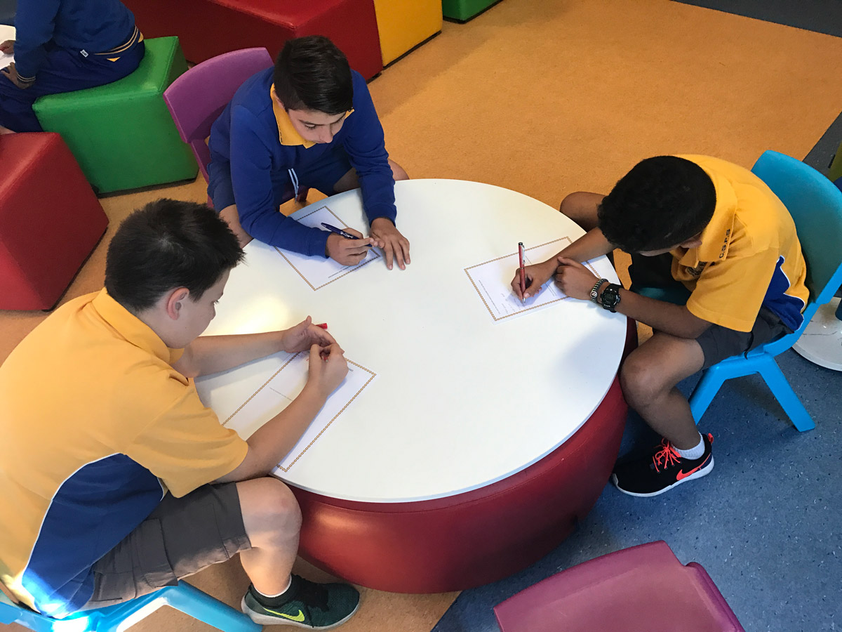 Three students writing on a round writable surface atop a large round ottoman