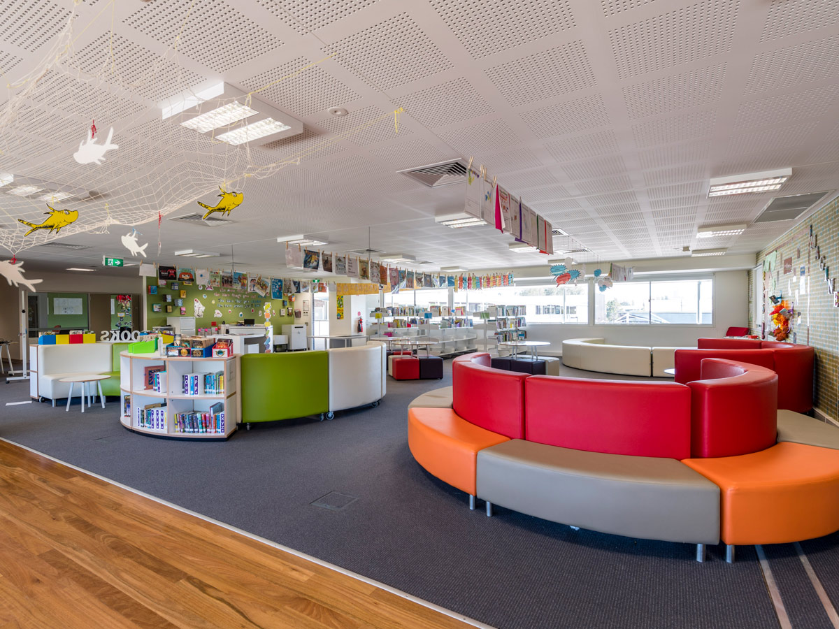 Colourful curved bench seating on wheels with wraparound bookshelves. Round tables with coloured soft ottoman seating