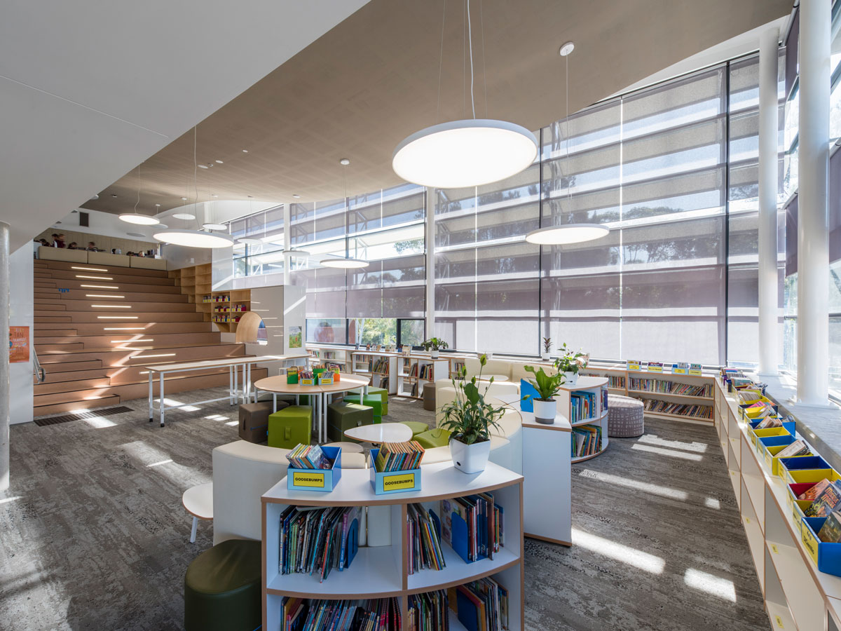 A bright double storey library support space with a central staircase and tiered seating. Furnished with curved bench seating with wraparound bookcases, round tables and soft ottoman seating