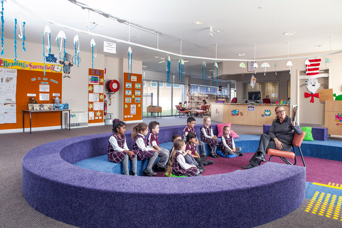 Students seated on large curved, tiered amphitheatre soft seating listening to teacher