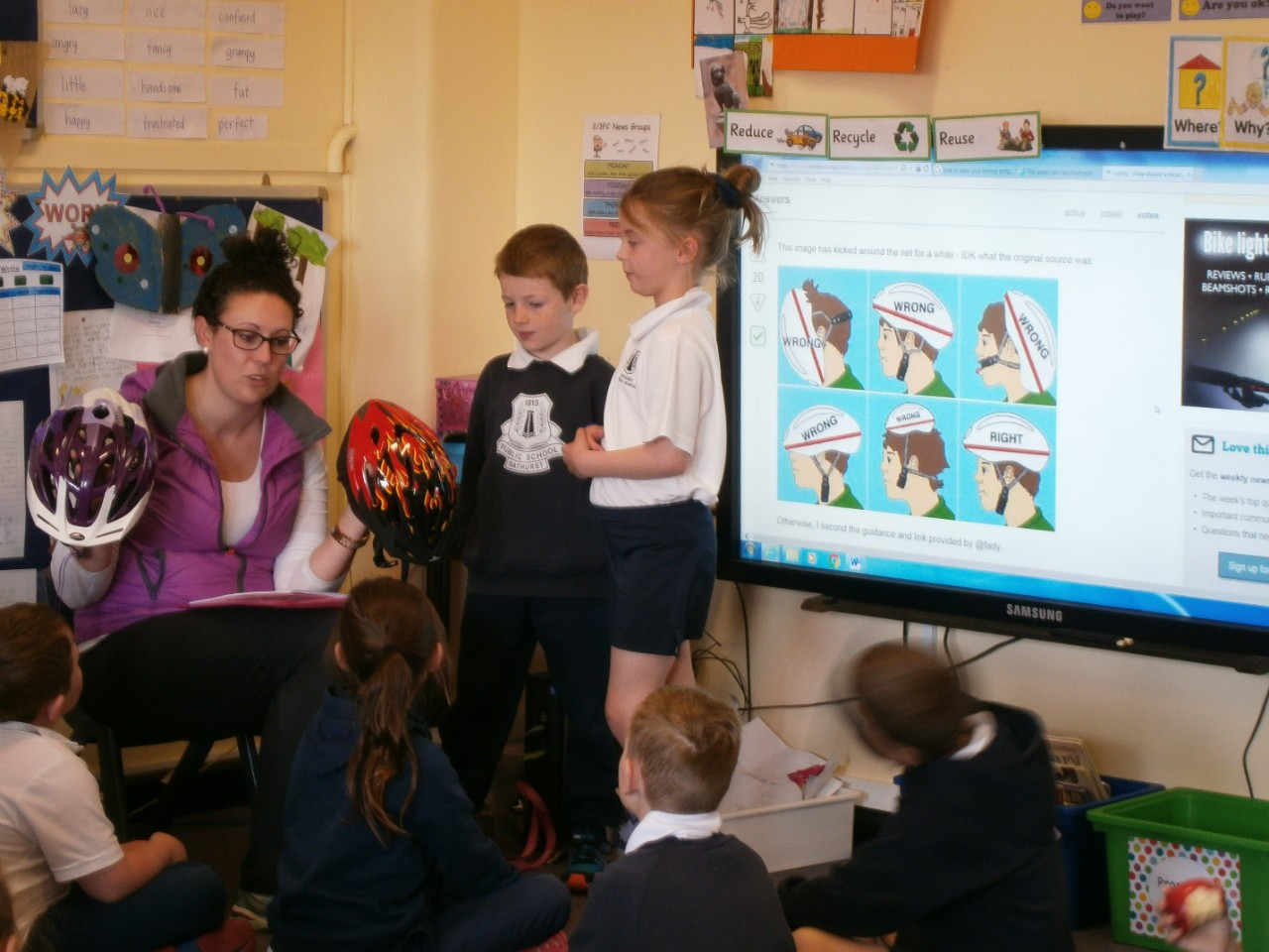 Teacher showing students some helmets with information about how to properly wear a helmet on a TV monitor.