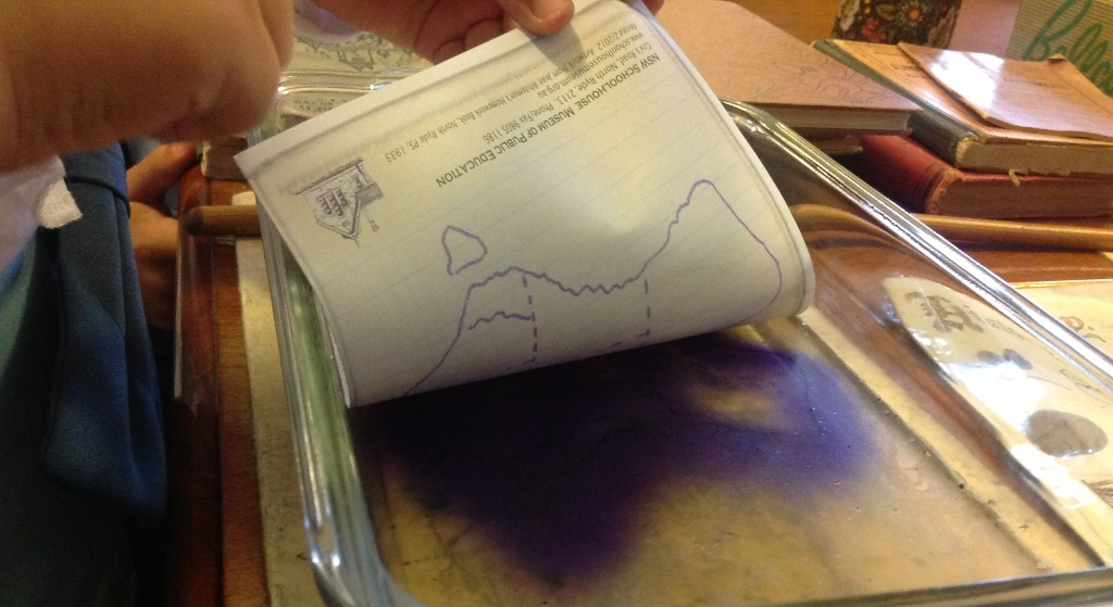 A student prints a map from a gelatin hectograph
