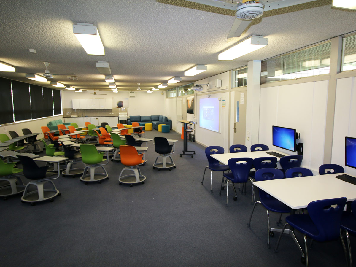 Large space with multiple zones inlcuding technology hub with rectangular table on wheels with large display monitors around perimeter and audience setting with colourful lecture chairs on wheels