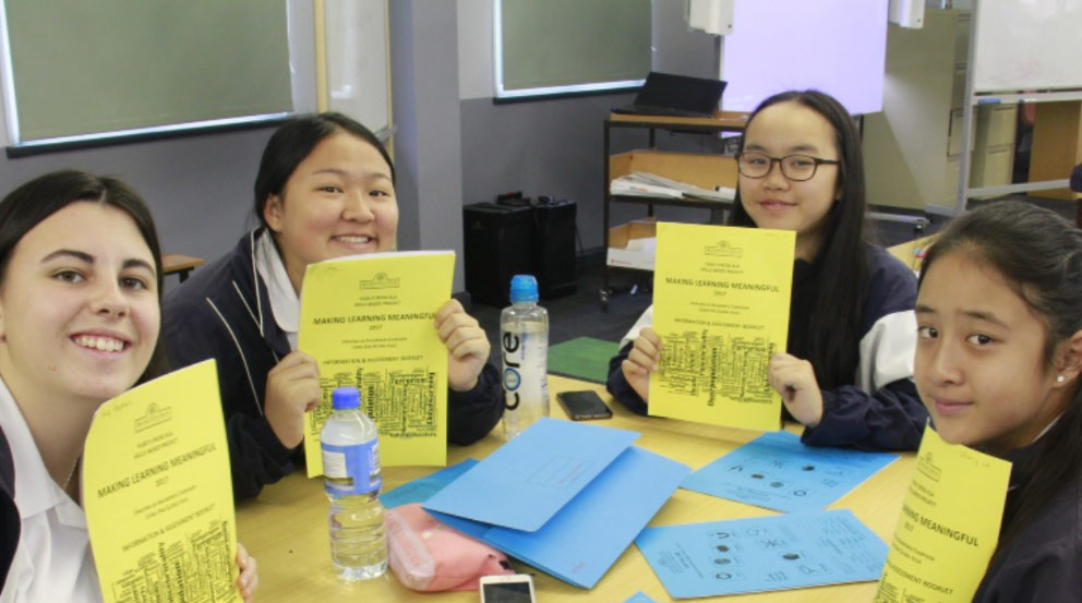 Four female students holding up a sheet of paper titled - making learning meaningful