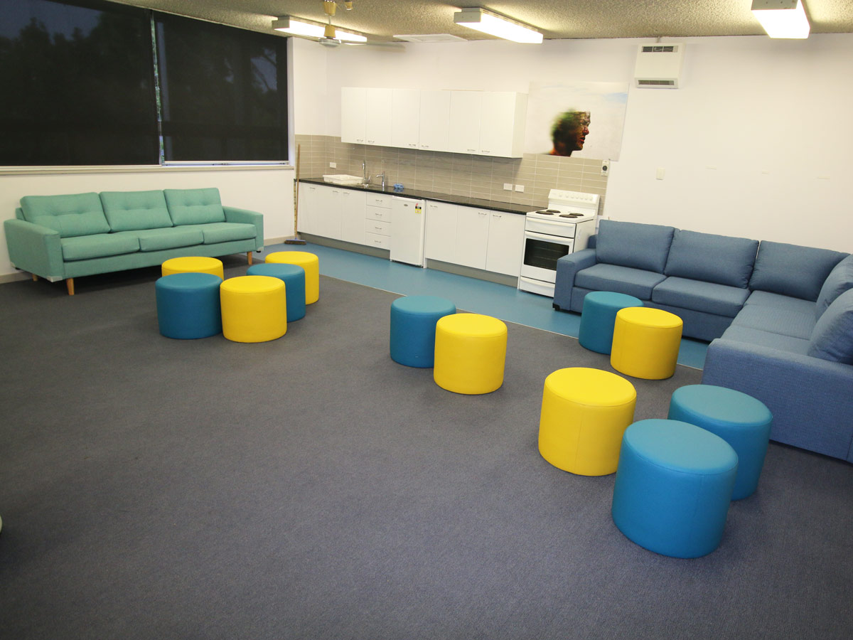 Lounge seating with soft, lightweight ottomans in a large open space with kitchen facilities
