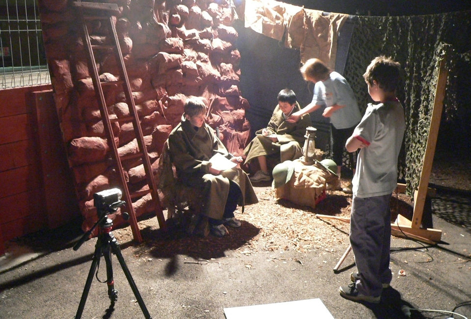 Students filming an evening war scene with key light