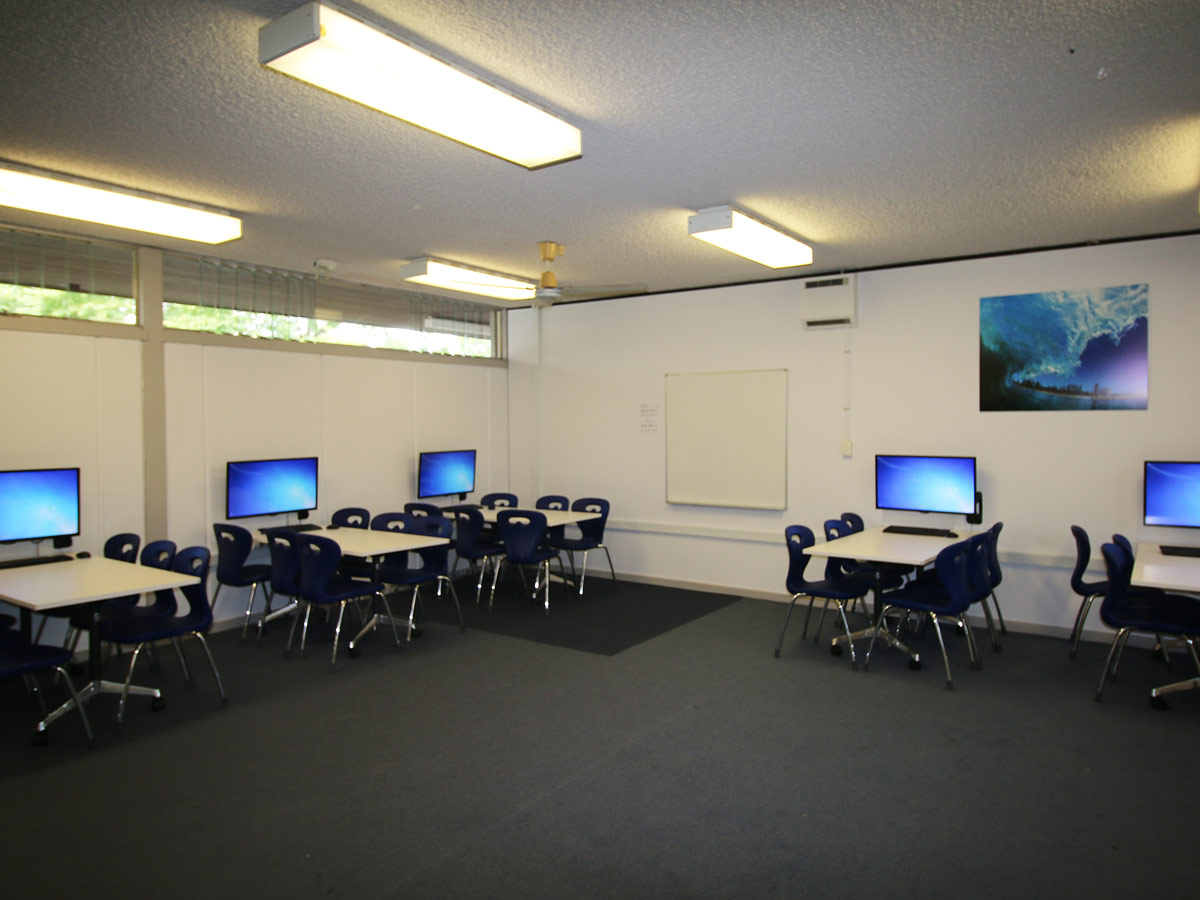 Large space with large rectangular tables on wheels around perimeter with large computer display at each group table