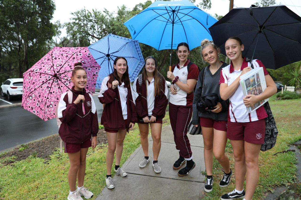 Group of six students with umbrellas.