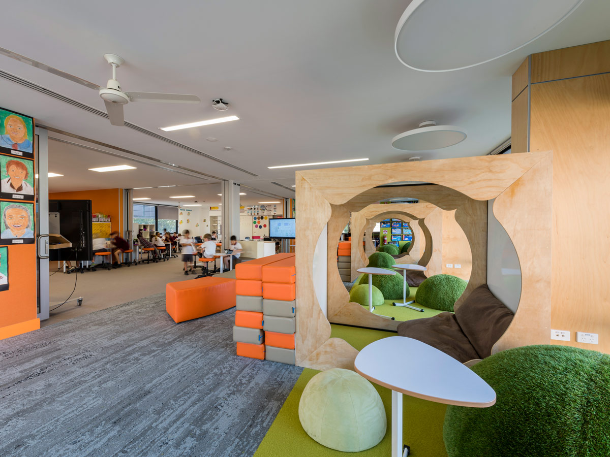 Bright and colourful breakout zone next to learning space. Green seating domes with small mobile desks sit within pods separated by timber frames. Colourful jenga block are available for extra seating and work space