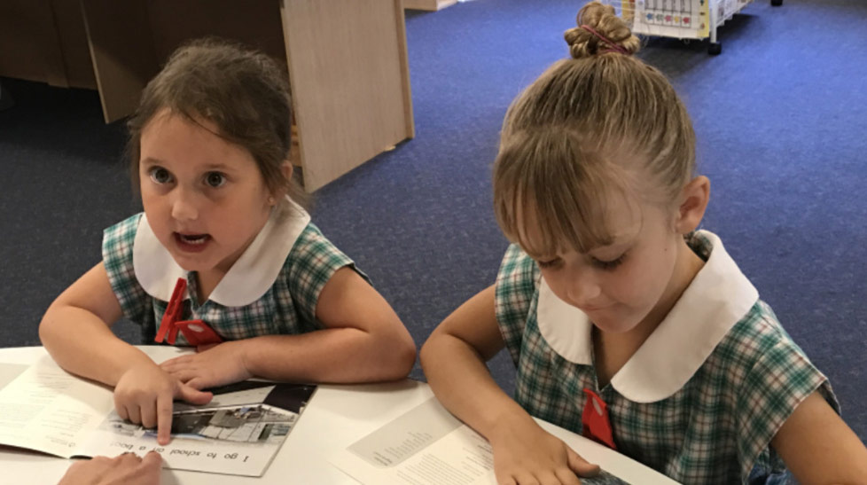 Two young female students reading together