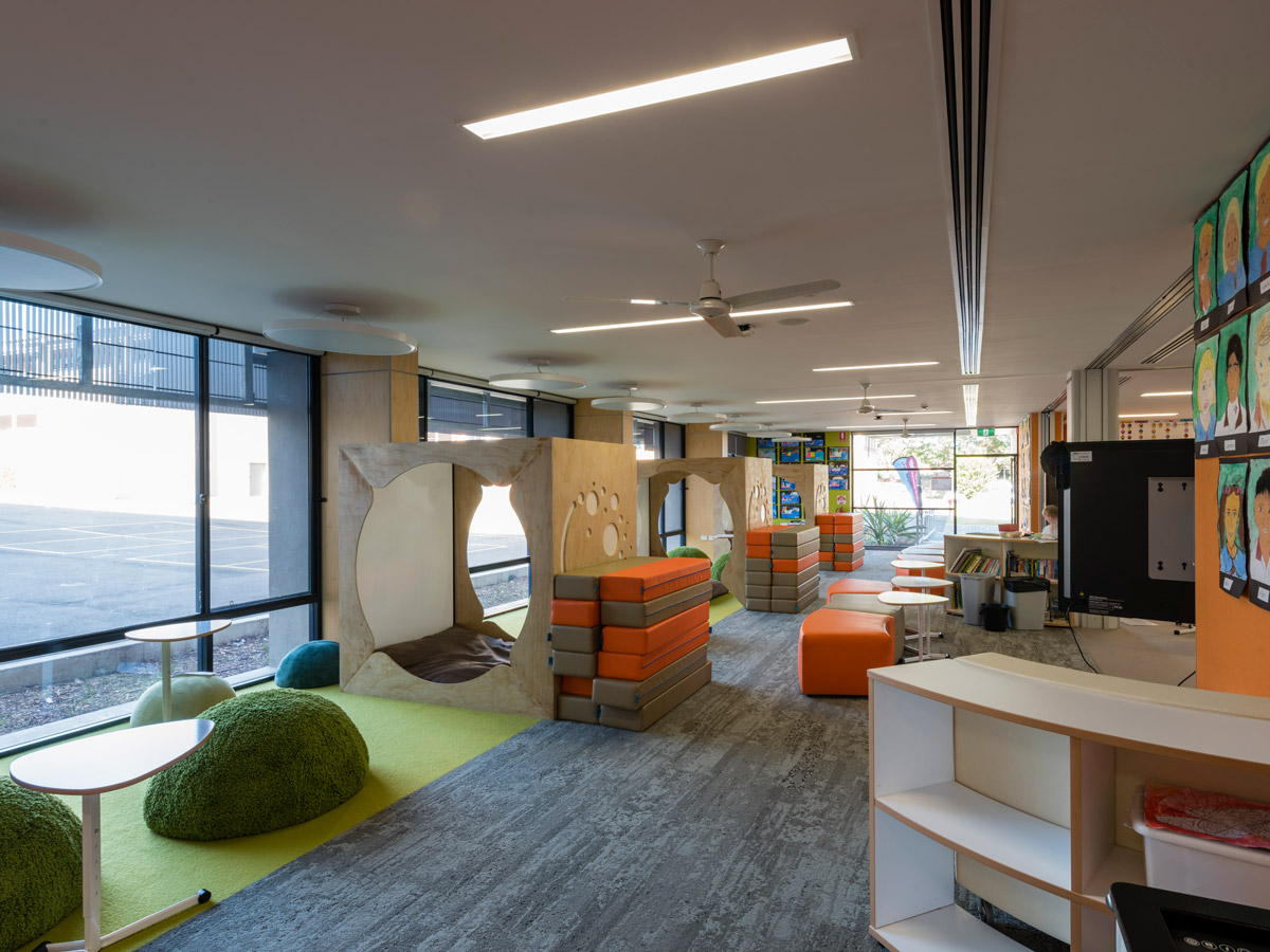 Breakout zone with green seating domes, jenga blocks for mobile seating and workspace, and small mobile desks. Small bookcases with storage line the opposite side of the room