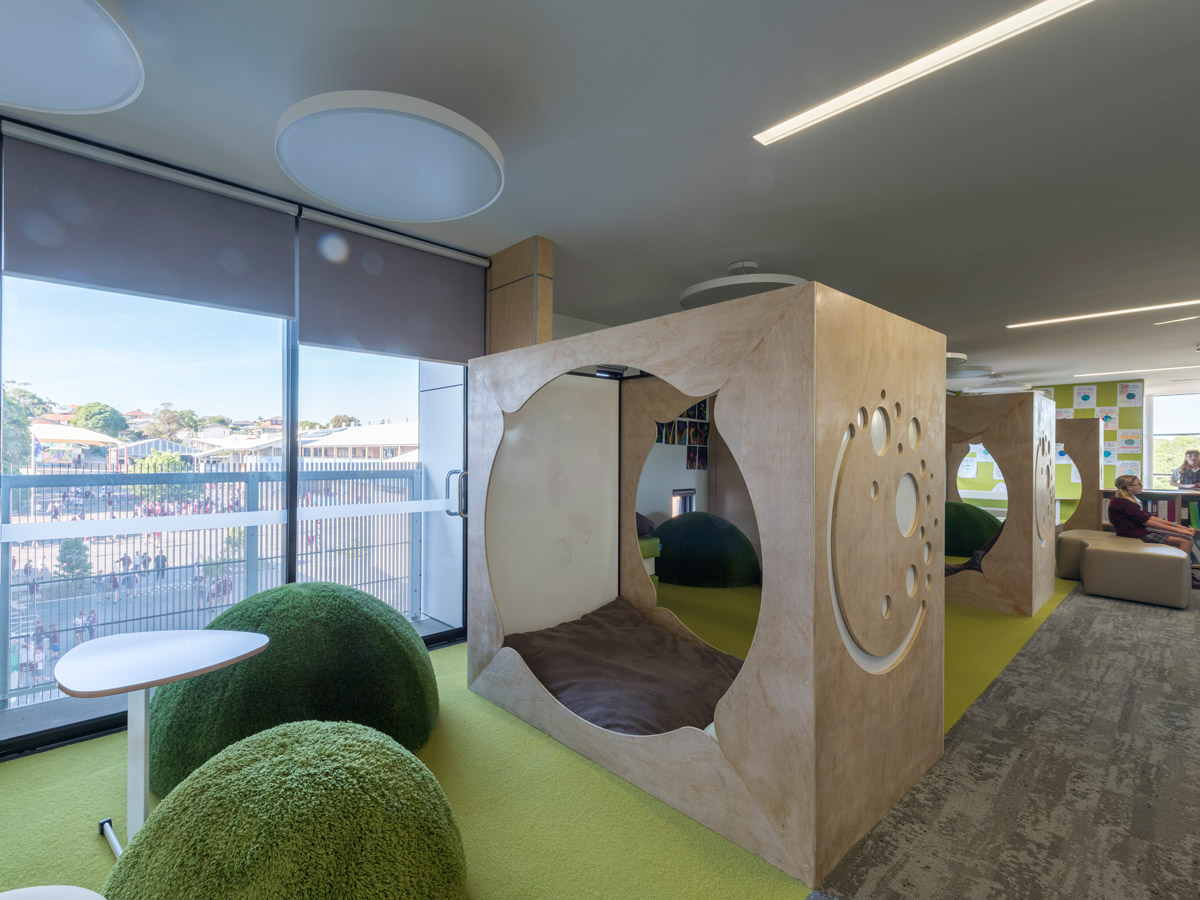 Breakout zone with timber framed pods with beanbag seating. Green seating domes line the outside of the spaces with small mobile desks