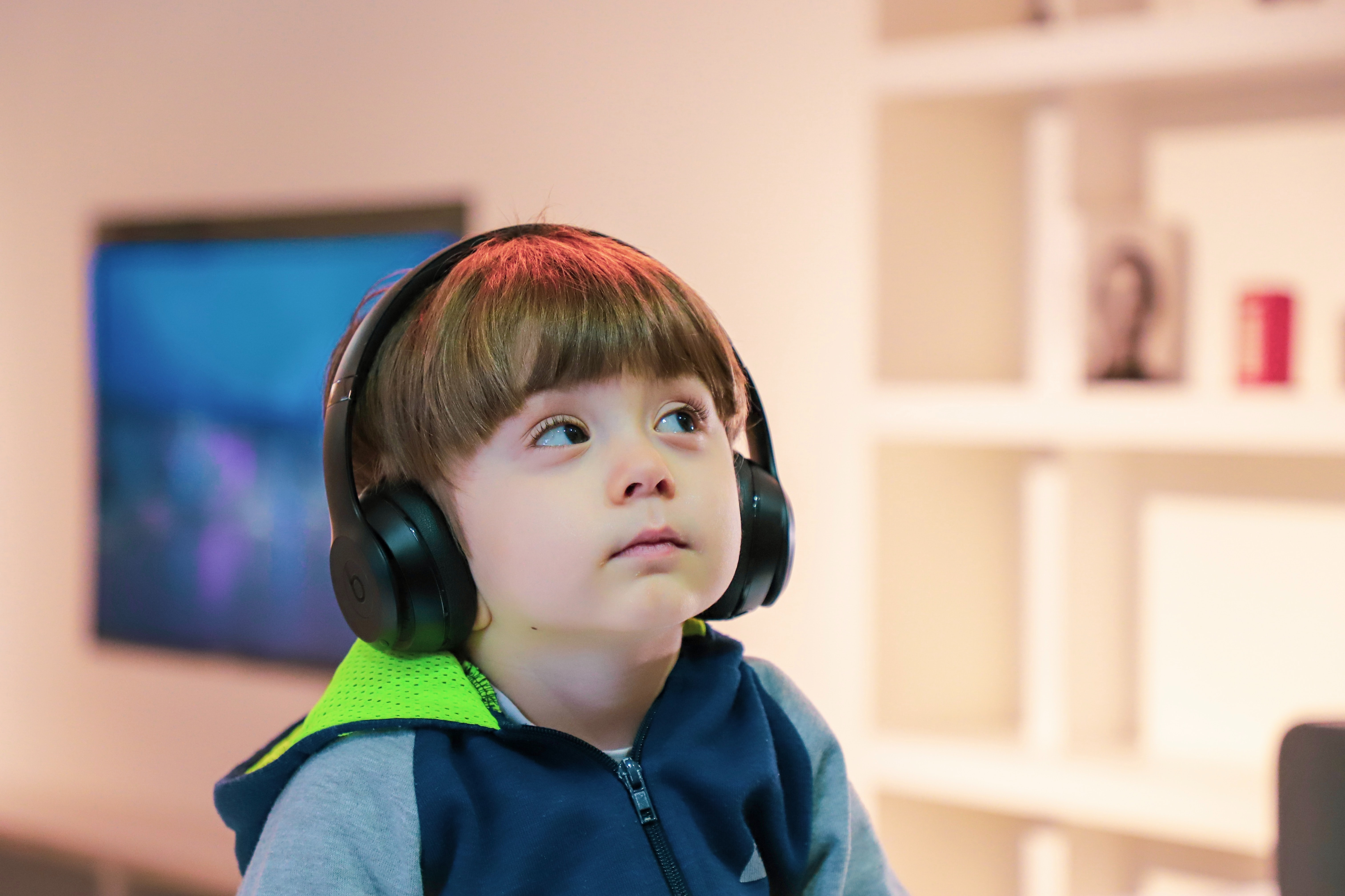 young child looking at a screen with headphones on.