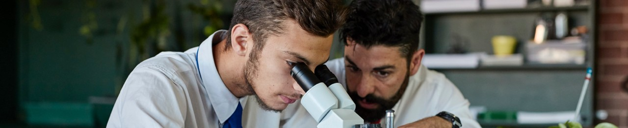 High school students looking through microscope