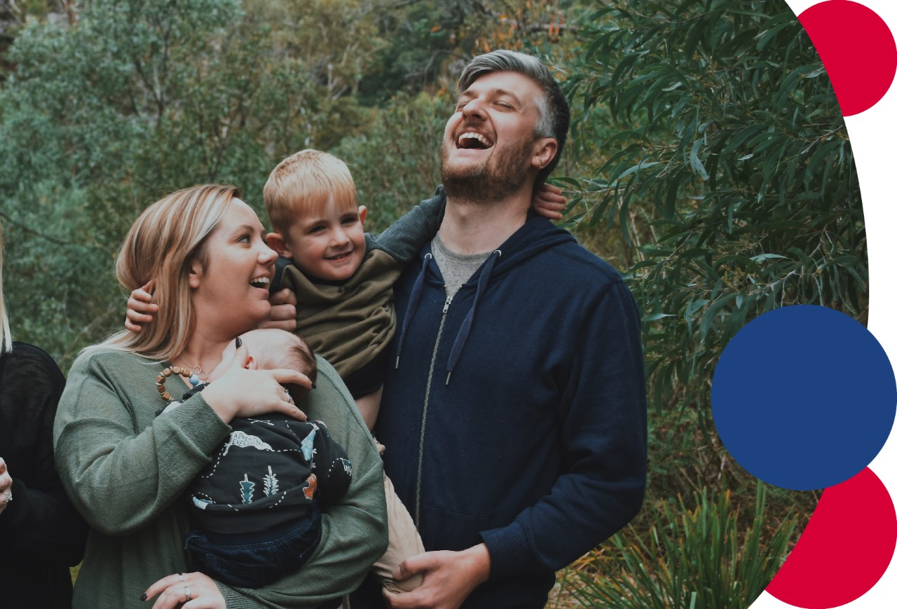 A family laughing together while on a bushwalk.
