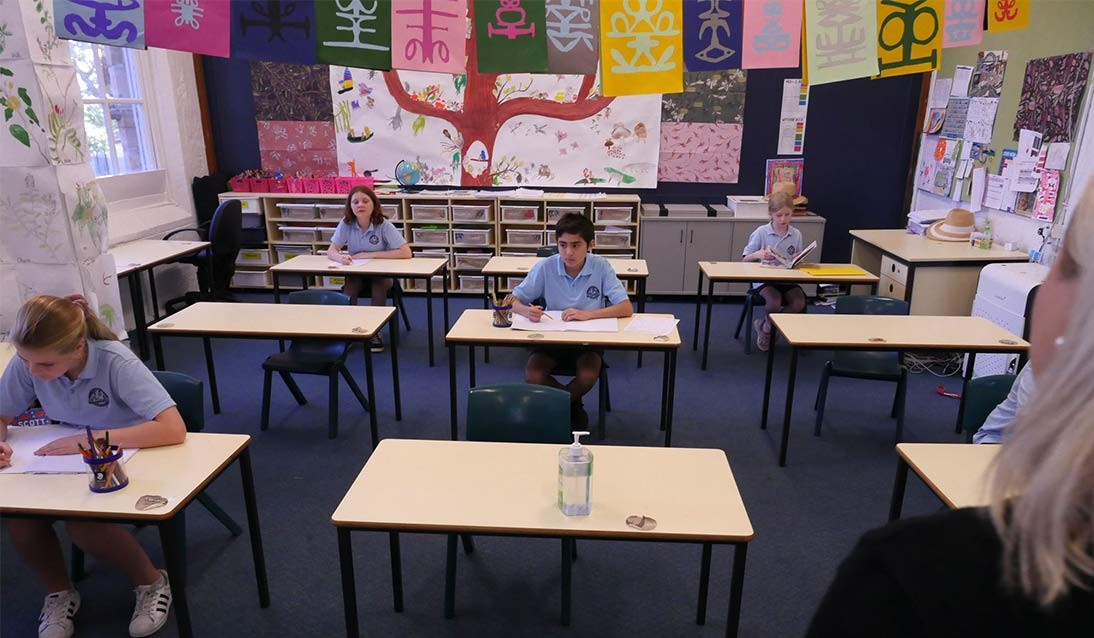 Students sit one desk apart from each other in the classroom.