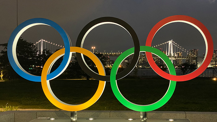 Olympic rings on dark night city background.