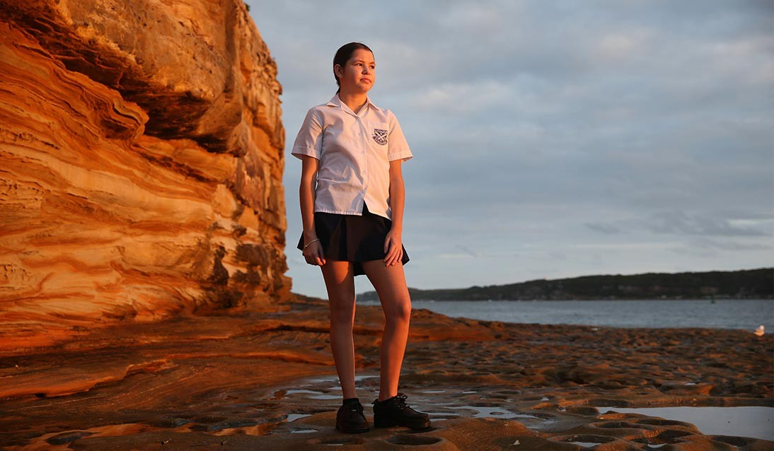 A teenage girl stands on a rock shelf overlooking the water.