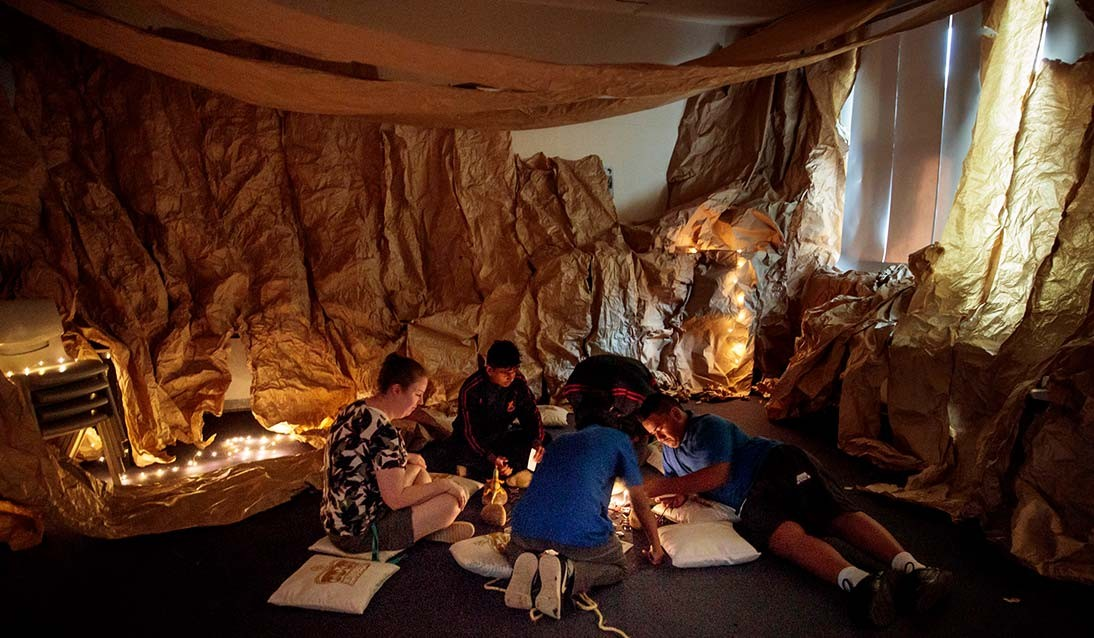 A group of students sit on the floor of a cave made of butchers paper and fairy lights.