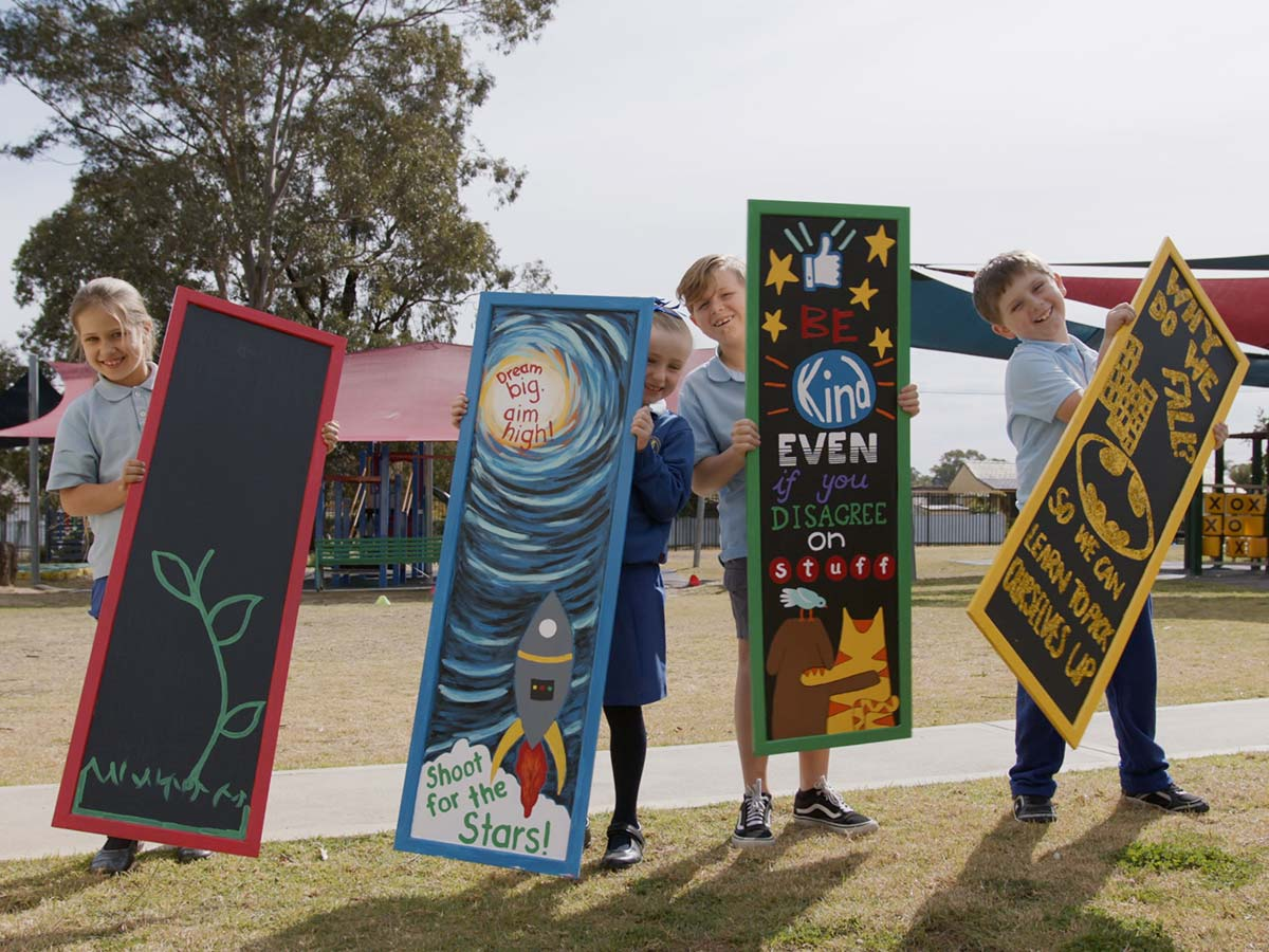 Students holding toilet doors painted with creative designs