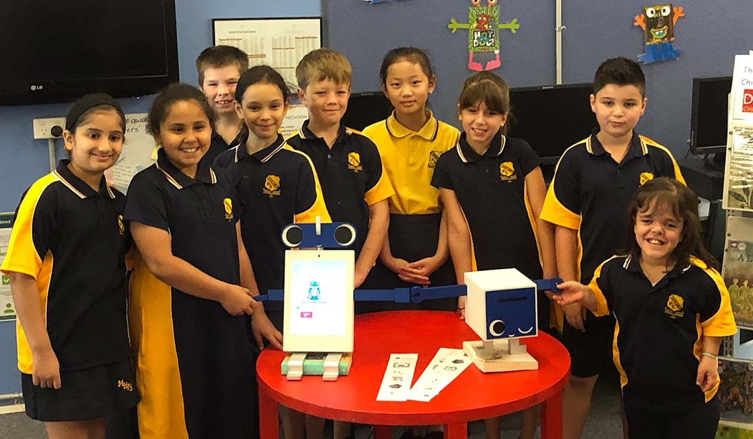Group of students standing behind the book bot