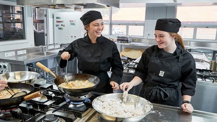 Two female students cooking in a school kitchen