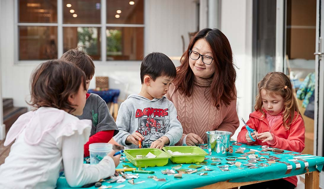 An early childhood educator sits at a table with four preschoolers working on a craft activity.