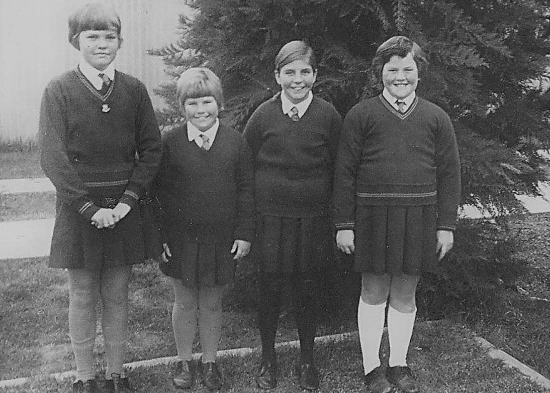 Black and white photo of four students standing outside.