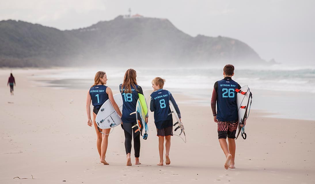 Four students walking away from the camera on the beach with surfboards