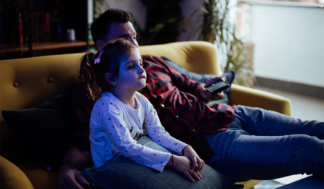 A child and father watching television.