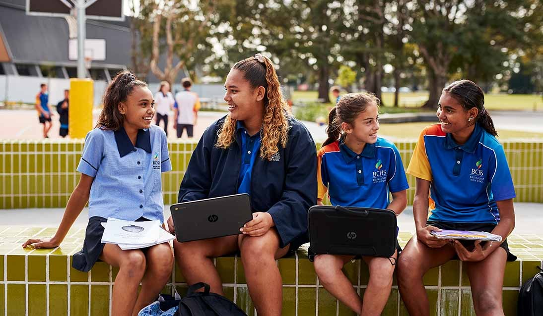 Four high school girls sit together outside looking at notes on their laptops.