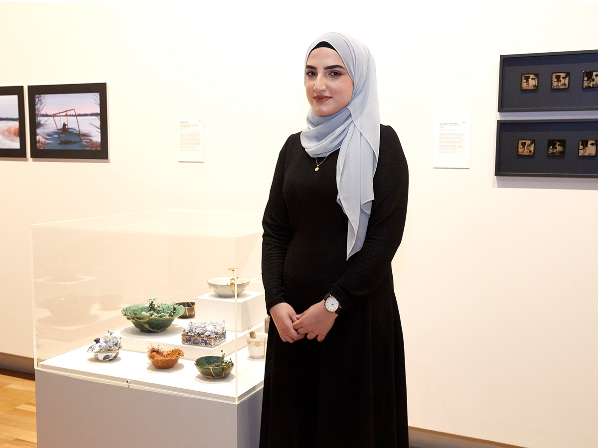 Young woman with a head scarf stands next to display of her artworks