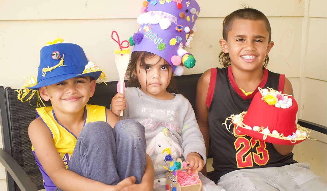 A group of students wearing decorated hats.