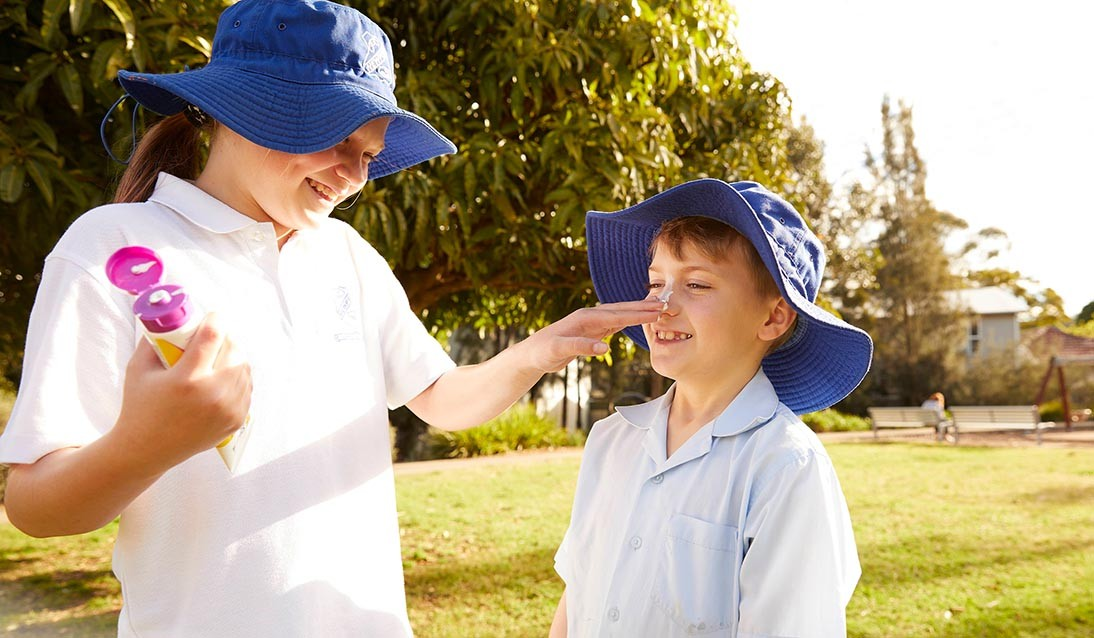 A female student wearing a blue wide brim hat applies sunscreen to the nose of a male student wearing a blue brim hat.