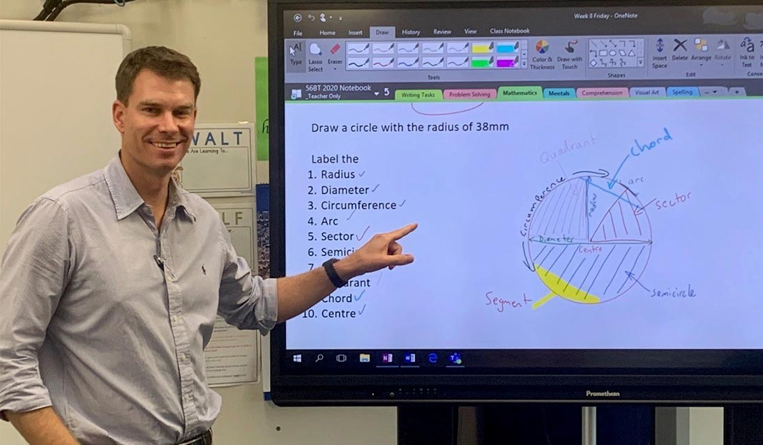Brendan Taylor standing in front of a large computer screen with maths work in OneNote.