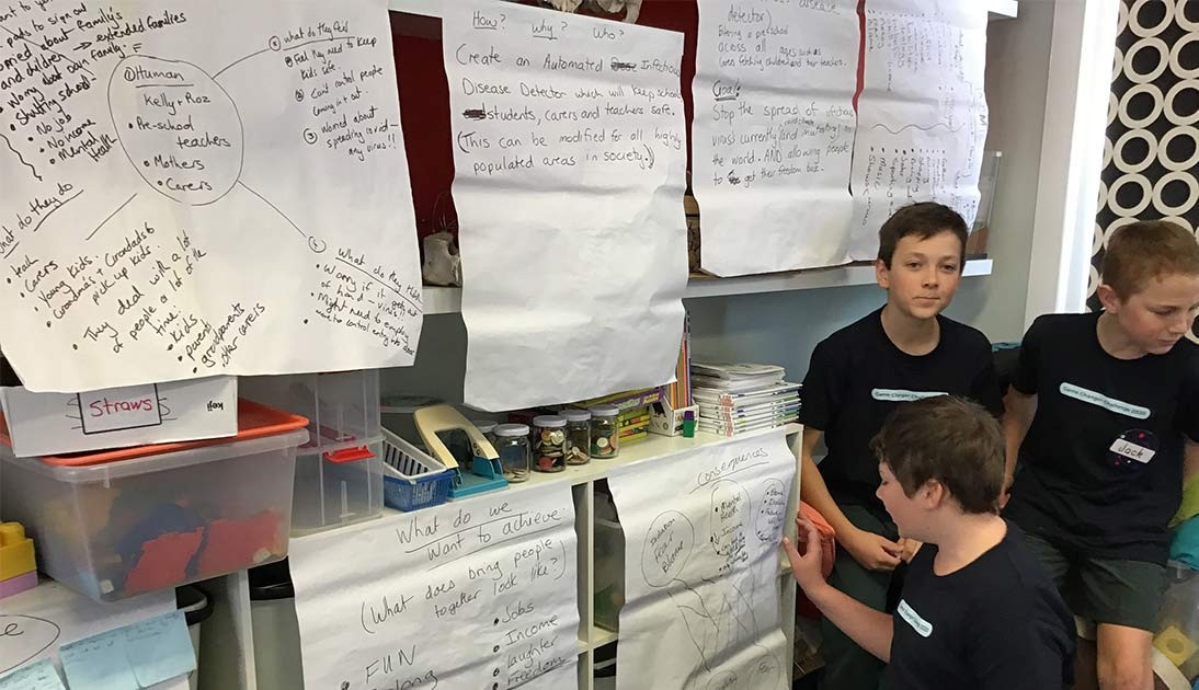 A group of three boys working together in front of a wall of paper
