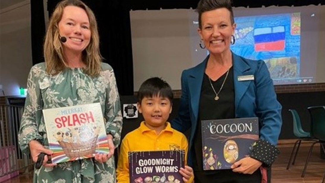 Two adults stand with a child between them, all three are holding picture books.