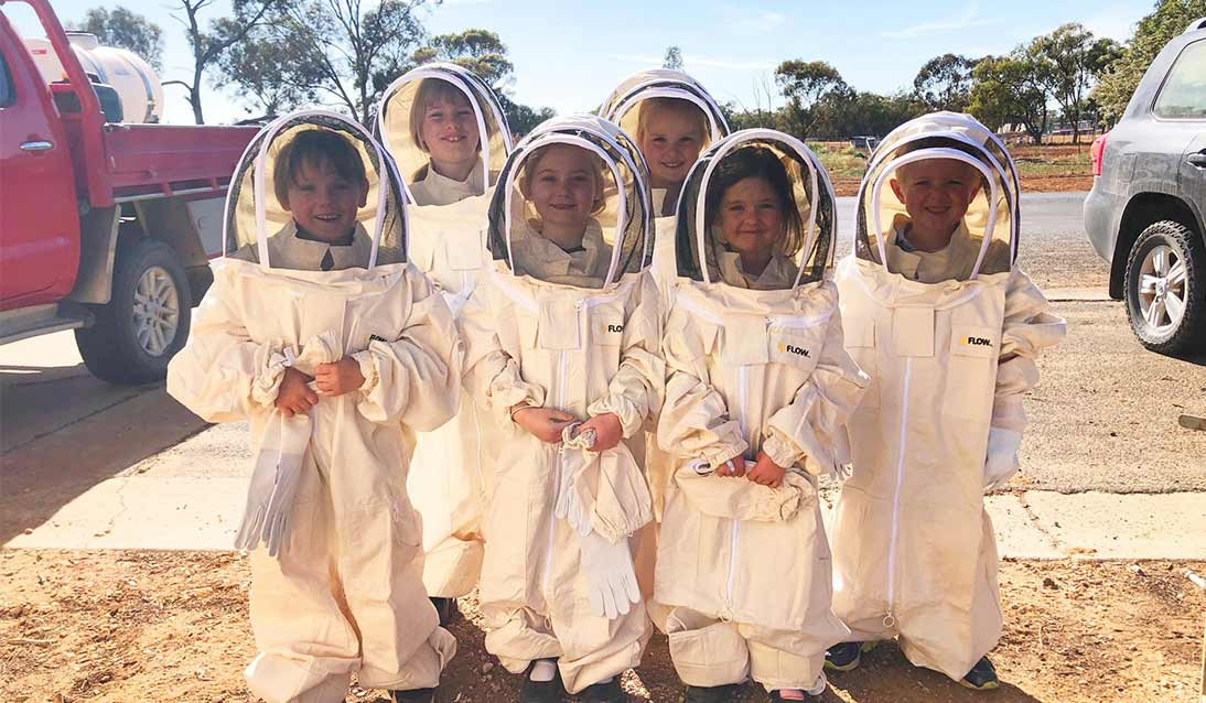 Students wearing beekeeping suits.