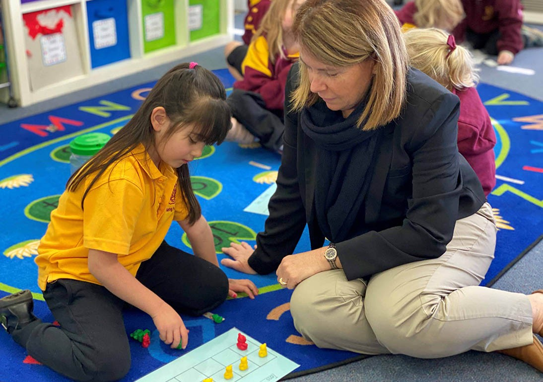 Woman and child sitting on the floor of a classroom using maths counters.
