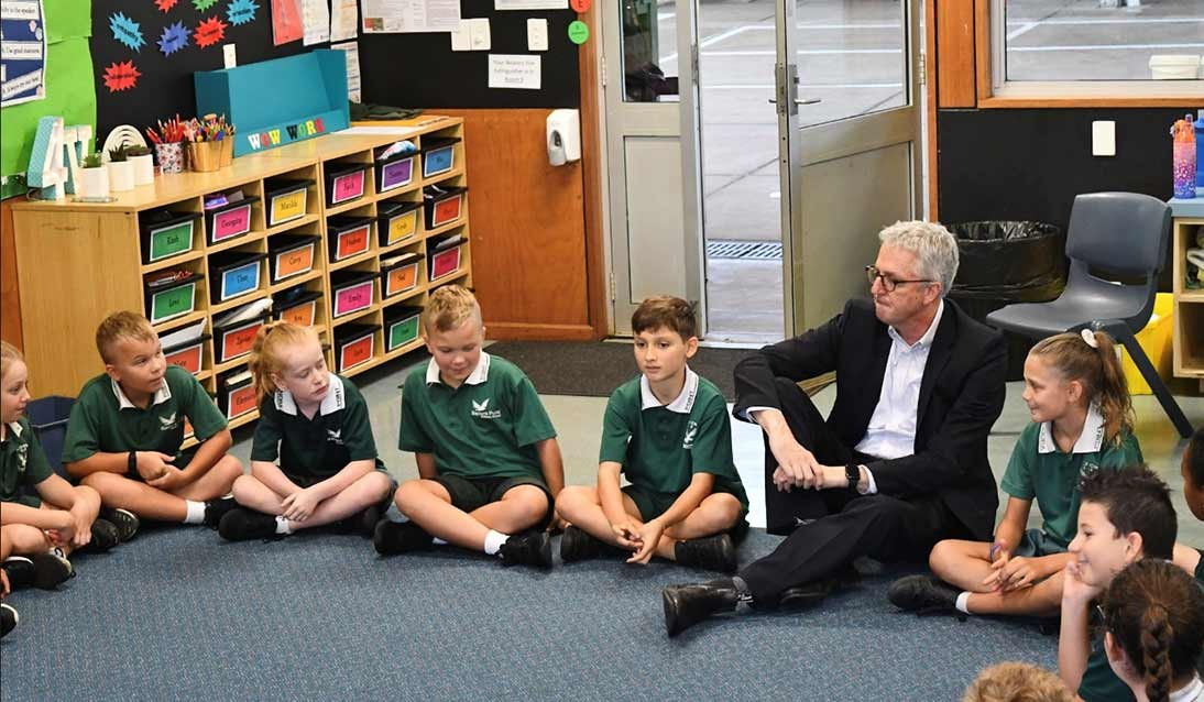 Mark Scott sitting on the floor with students