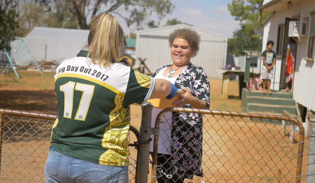 A woman wearing a Menindee Central School shirt hands a box of food over a fence to another lady.