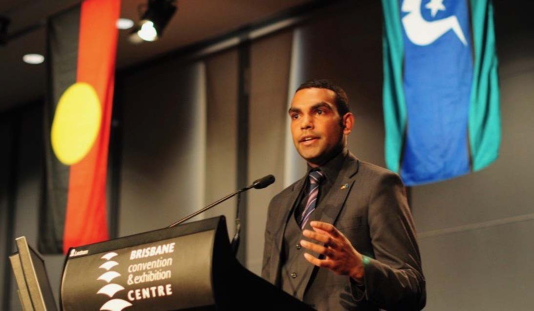 Man wearing a suit stands in front of a lecturn and microphone. Aboriginal flag and Torres Strait Island flag hangs from the ceiling behind him.